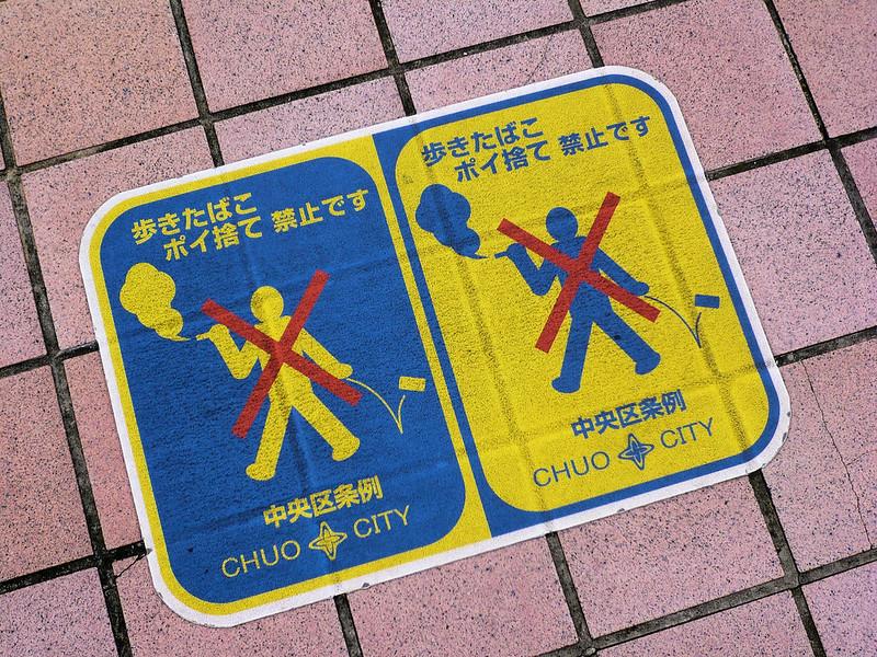 Un divieto di colore blu e giallo in cui si vieta, nella città di Chuo, di fumare e buttare i rifiuti a terra mentre si cammina.