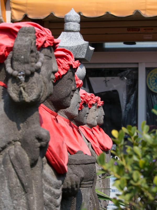 Kasa Jizō o statue del bodhisattva Kṣitigarbha in un tempio. Hanno dei capellini e una tovaglietta di colore rosso.